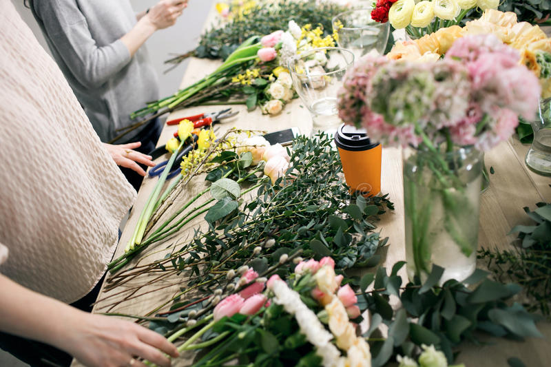 Workshop florist, making bouquets and flower arrangements. Woman collecting a bouquet of flowers. Soft focus royalty free stock images