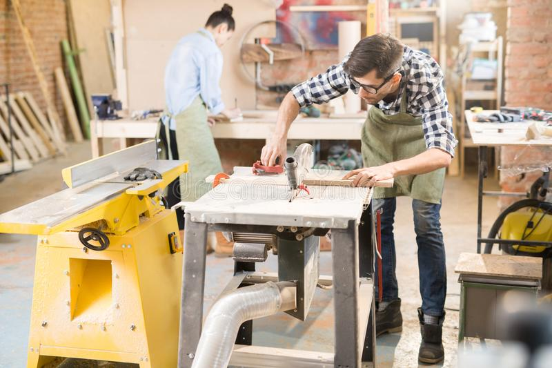 Workshop in Joinery. Full length portrait of focused modern carpenter working with wood in joinery shop, copy space royalty free stock photography