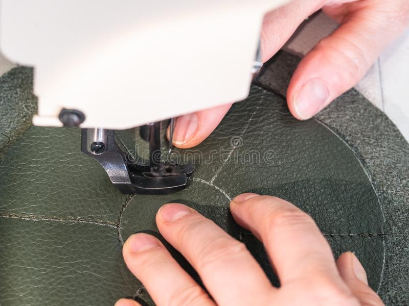 Craftsman stitches the bottom on sewing machine royalty free stock photography