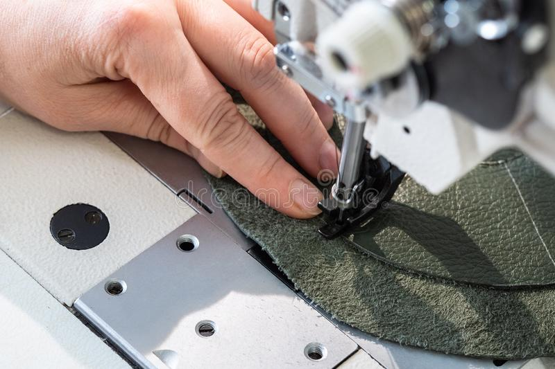 Craftsman stitches the layers on sewing machine royalty free stock image