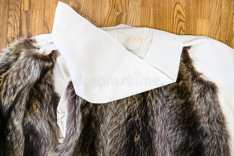 The coat layout with stitched fur pelts on table. Workshop of manufacturing of coats from raccoon fur - the coat layout with stitched fur pelts on table royalty free stock photo