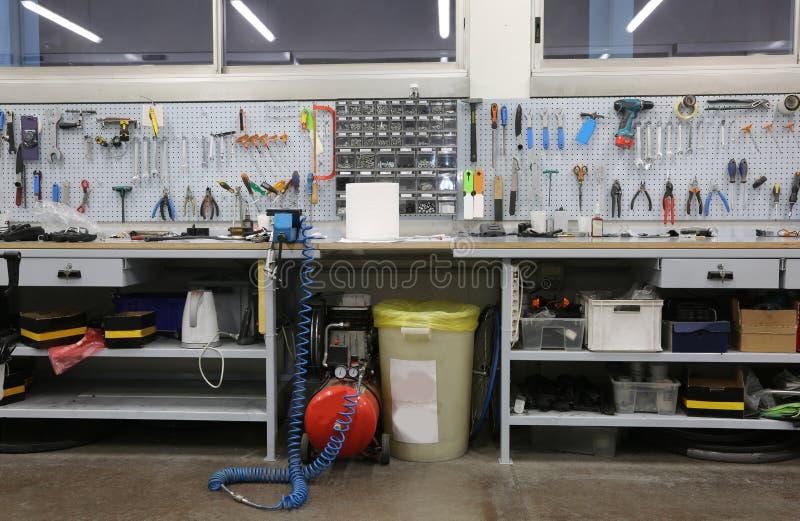 workshop met grote werkbank en een groot aantal hulpmiddelen voor ma stock foto's