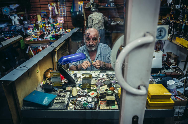 Workshop in Tbilisi. Tbilisi, Georgia - July 18, 2015. Man works in traditional clockmaker workshop in Tbilisi stock photos