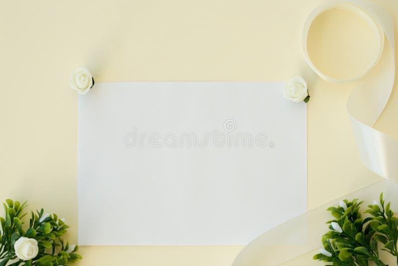 workspace Κάρτα γαμήλιας πρόσκλησης, κορδέλλα σατέν, άσπρα τριαντάφυλλα και πράσινα φύλλα στο μπεζ υπόβαθρο Υπερυψωμένη όψη Επίπε στοκ εικόνα με δικαίωμα ελεύθερης χρήσης