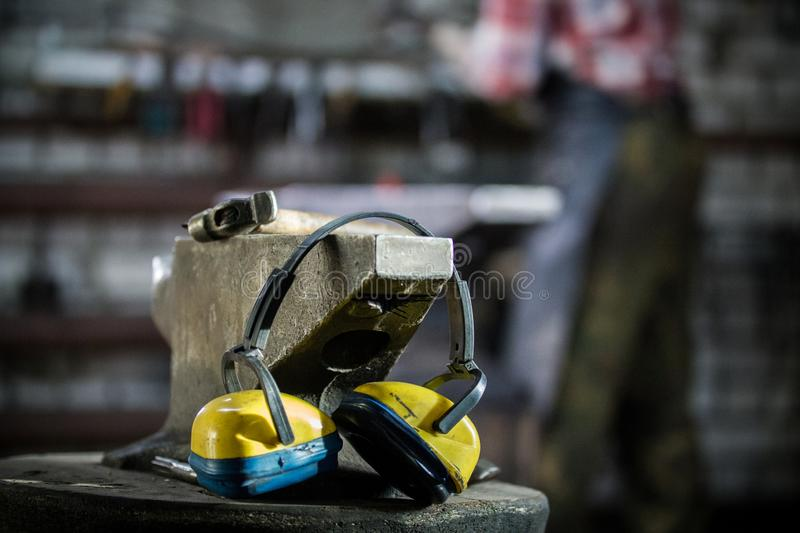 Workspace of blacksmith at forge. the hammer, headphones and gloves lie on the anvil. Close up shot stock images