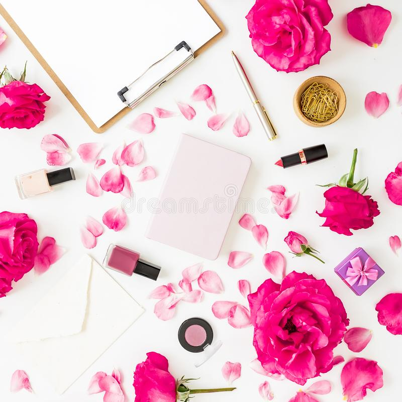 Workspace with clipboard, pastel roses, cosmetics and accessories on white background. Flat lay, top view. Workspace with clipboard, pastel roses, cosmetics and stock photography