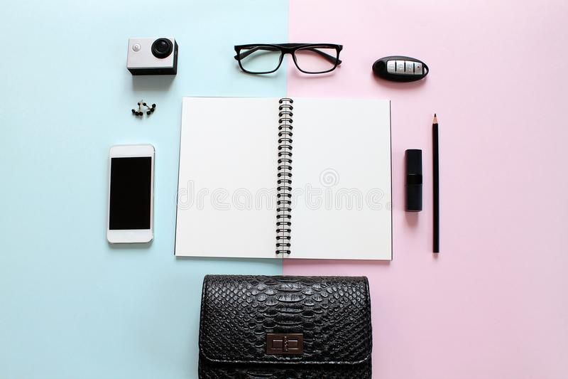 Workspace desk with blank notebook, pencil, lipstick, car key, eye glasses, small action camera, earrings, bag and smart phone on stock photography