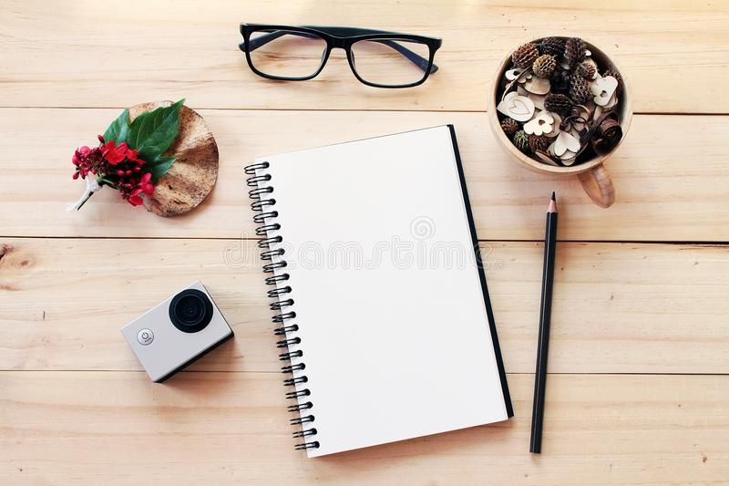 Workspace desk with notebook, pencil, pine cones in tea wooden cup, eye glasses, red flower and small action camera on wooden back stock photos