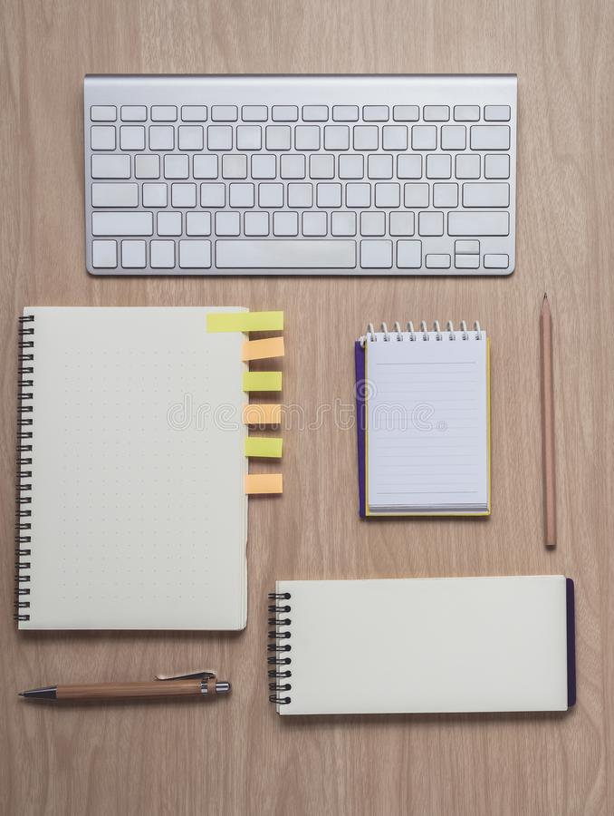 Workspace with diary or notebook and clipboard, keyboard, pencil, sticky notes on wooden background royalty free stock images