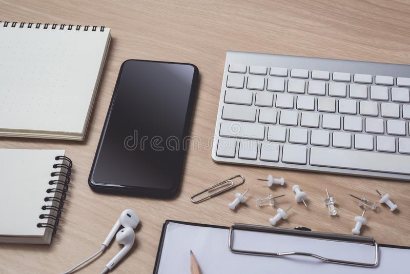 Workspace with diary or notebook and clipboard, mouse computer, keyboard, smart phone, Earphone, pencil, pen on wooden background stock photos