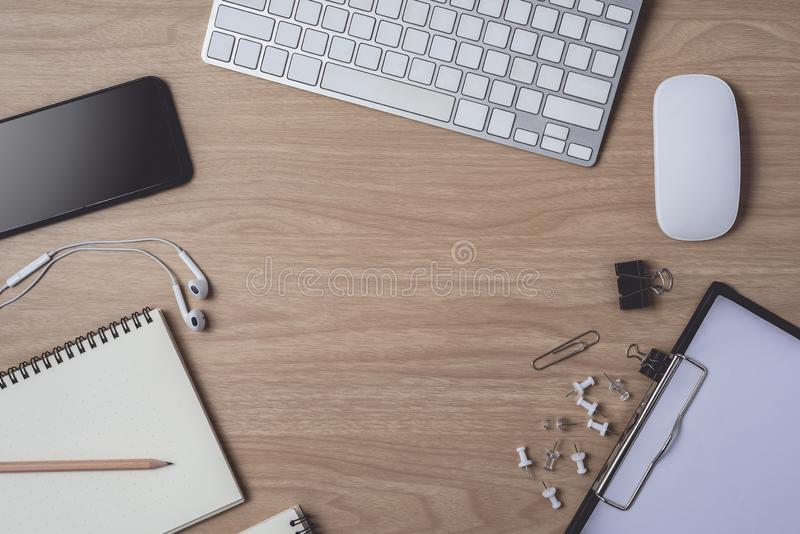 Workspace with diary or notebook and clipboard, mouse computer, keyboard, smart phone, Earphone, pencil, pen on wooden background stock photo