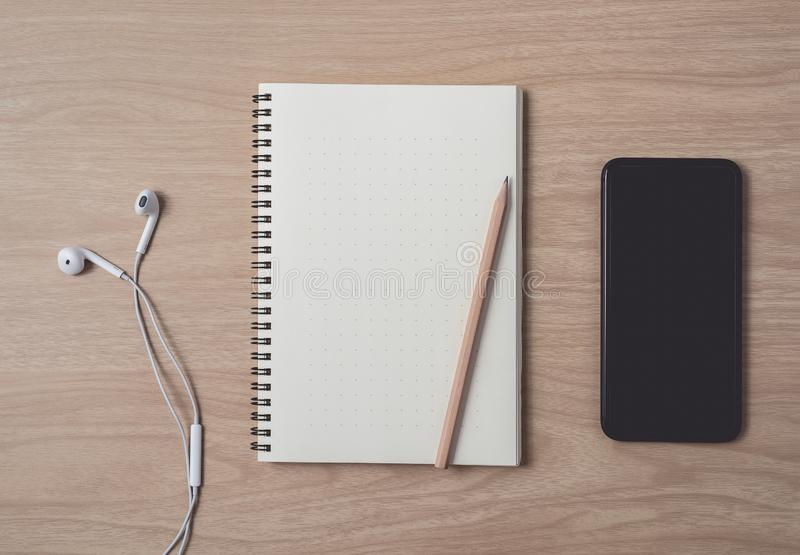 Workspace with diary or notebook and smart phone, Earphone, pencil, pen on wooden background stock photos