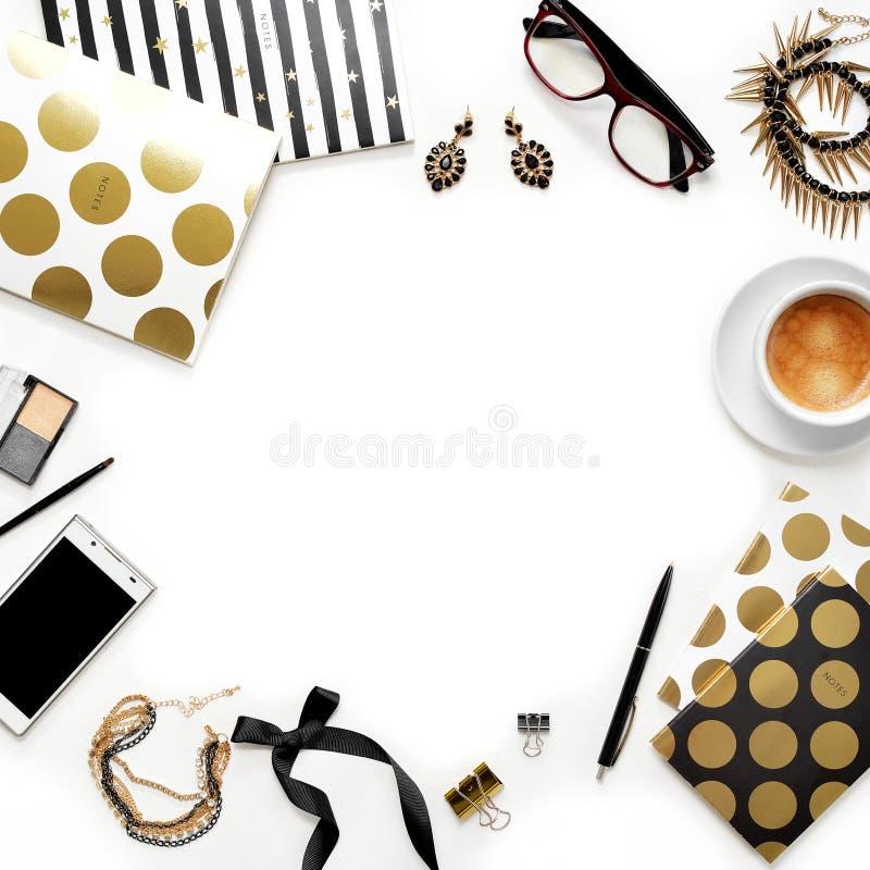 Workspace för inrikesdepartementet för lekmanna- mode för lägenhet kvinnlig med telefonen, koppen kaffe, stilfulla svarta guld- a arkivbilder