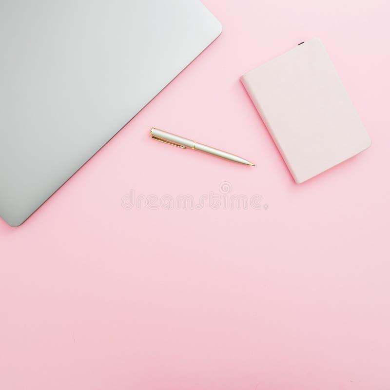 Workspace för inrikesdepartementetskrivbord med bärbara datorn, anteckningsboken och pennan på rosa bakgrund Top beskådar Lekmann royaltyfri foto