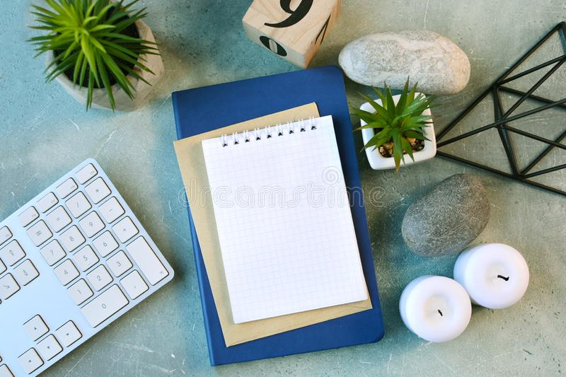 Workspace flat lay with empty notebook page, computer keyboard, flowers, candles, stones and other scandinavian decor. royalty free stock photo