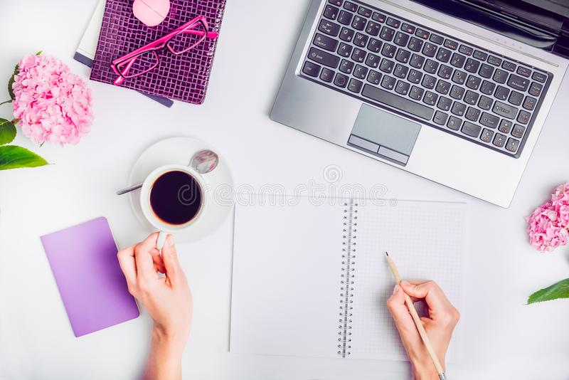 Workspace with laptop, girl`s hands writing in notebook, glasses, cup of coffee and wisteria flowers on white background. Top vie stock images