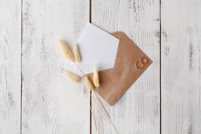 Workspace with laptop, handmade invitation lists, craft envelope, pen, twine, candles and watercolor paintings on white background. Overhead view. Flat lay royalty free stock photo