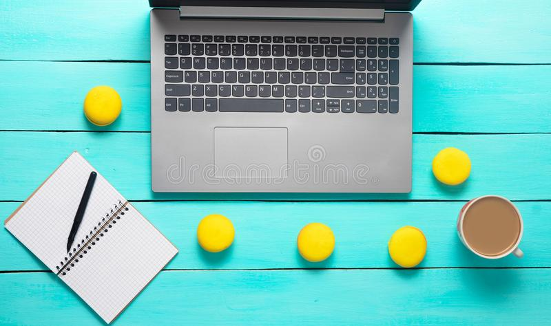 Workspace with laptop, notebook and pen. Morning breakfast with macaroons and a cup of coffee on a blue wooden table. royalty free stock image