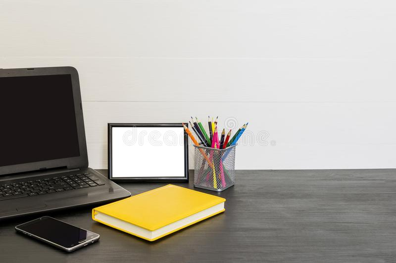 Workspace with laptop, yellow diary, photo frame, color pensils royalty free stock photos