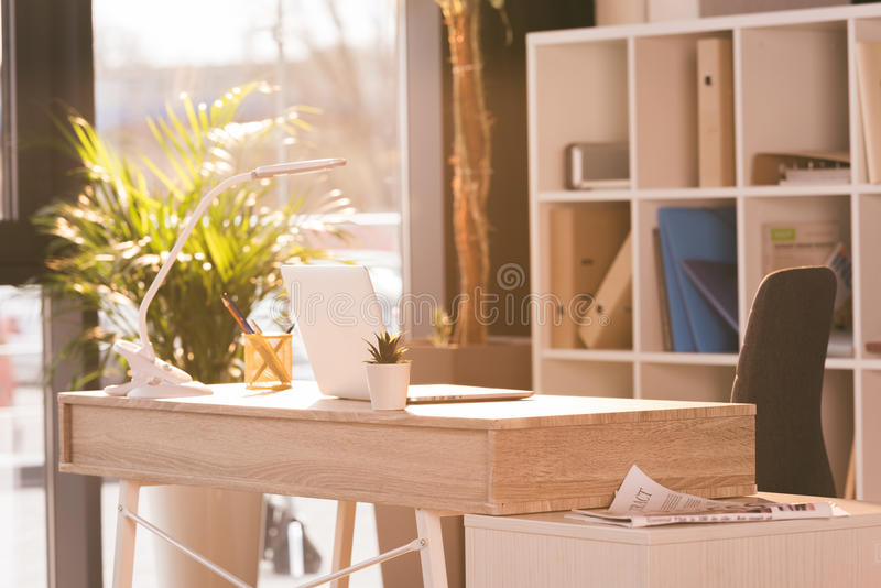 Workspace med bärbar datordatoren i modernt tomt kontor fotografering för bildbyråer