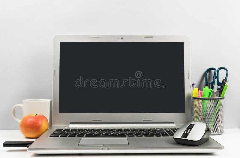 Workspace med bärbara datorn, den svarta skärmen, koppen kaffe, äpplet, USB exponeringen och blyertspennaasken arkivbilder