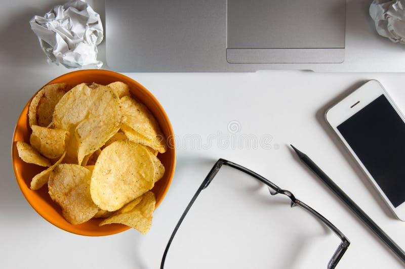 Workspace med bärbara datorn, skrynkligt papper och bunken av chiper på den wood tabellen Oskickbegrepp royaltyfri fotografi