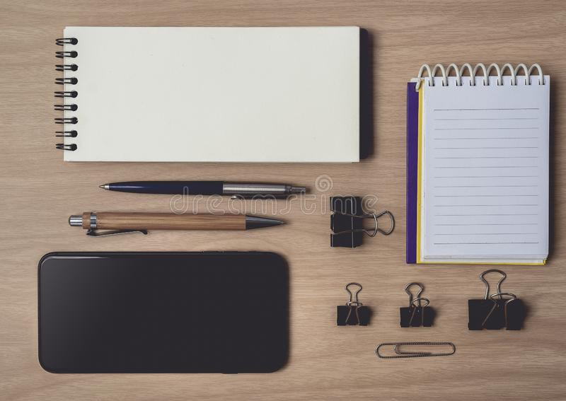 Workspace med dagboken eller anteckningsbok och skrivplatta, smart telefon, penna på träbakgrund arkivfoto