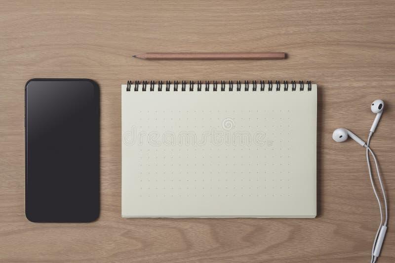 Workspace med dagboken eller anteckningsbok och smart telefon, h?rlur, blyertspenna, penna p? tr?bakgrund royaltyfri foto