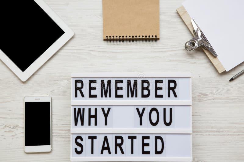 Workspace med minnestavlan, smartphonen, anteckningsboken, arket och ` minns därför du startade `-ord på lightbox över vit träbak royaltyfri fotografi