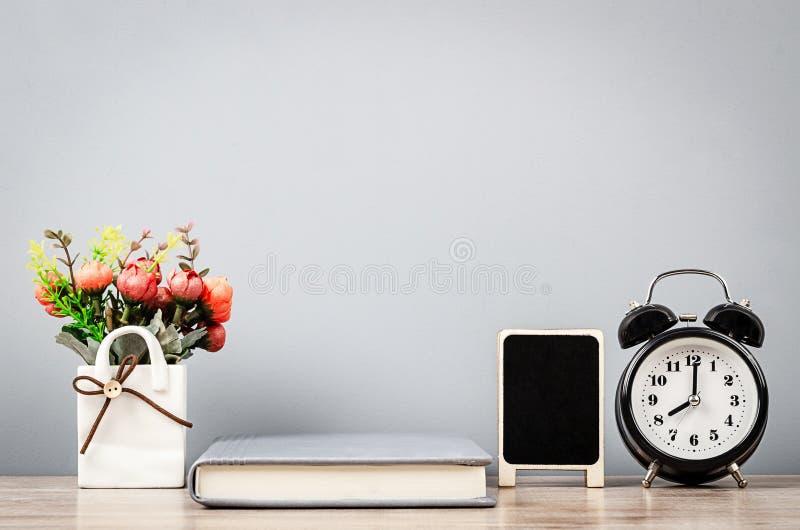 Workspace, notatnik i budzik z mini czernią, wsiadamy dla nutowego teksta zdjęcie stock