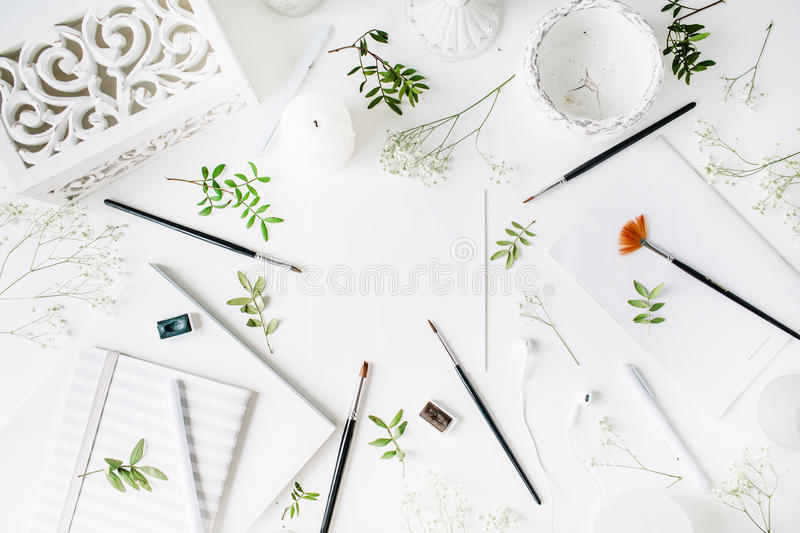 Workspace with notebook, sketchbook, brushes, clean paper, vintage casket, pen, candle and headphones royalty free stock photo