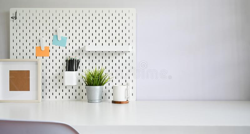 Workspace office supply and pegboard on white table copy space stock photography