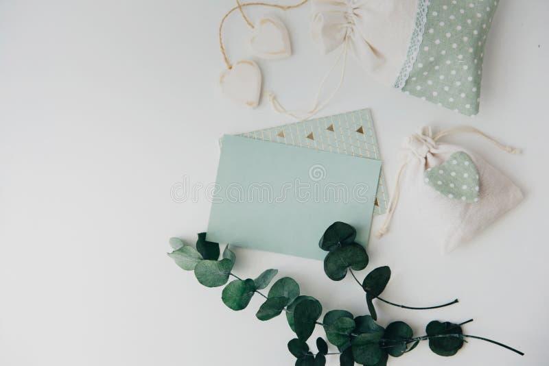 workspace Sidor för för bröllopinbjudankort och eukalyptus på vit bakgrund arkivfoto