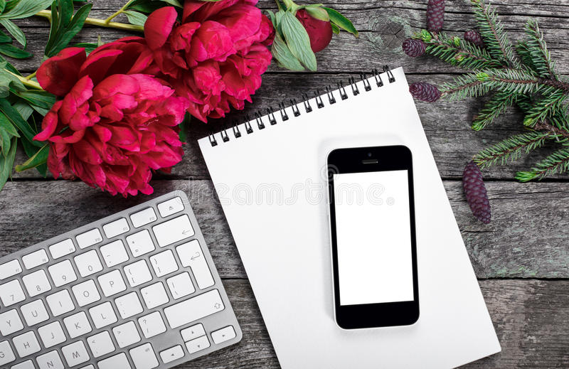 Workspace with smartphone, keyboard, notepad, fir branch and peonies flowers bouquet on rustic background stock photography