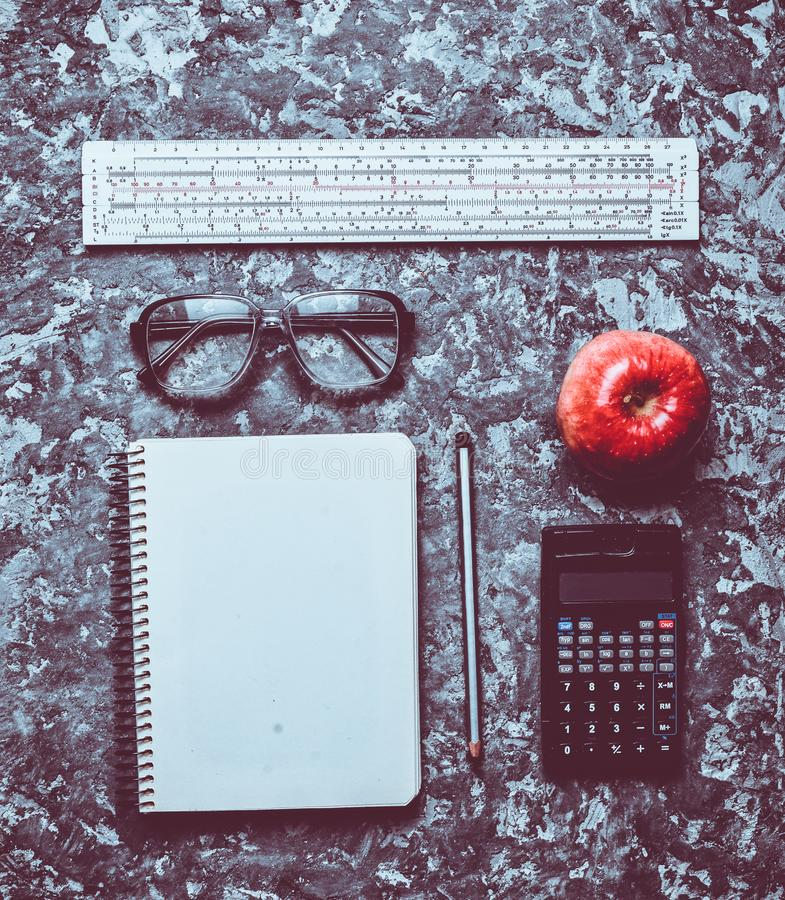 Workspace of a student engineer on a concrete surface. Loft style. Notepad, apple, calculator, pencil, glasses, ruler. Minimalism. And trend of gray color. Top royalty free stock image