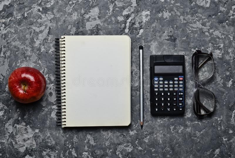 Workspace of a student engineer on a concrete surface. Loft style. Notepad, apple, calculator, pencil, glasses, ruler. Minimalism and trend of gray color. Top stock image