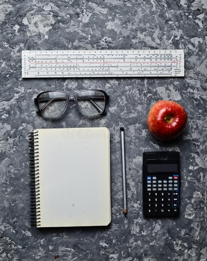 Workspace of a student engineer on a concrete surface. Loft style. Notepad, apple, calculator, pencil, glasses, ruler. Minimalism and trend of gray color. Top royalty free stock photo