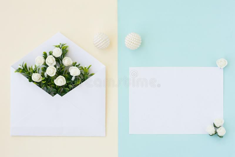 Workspace. Wedding invitation card, envelope, white roses and green leaves on beige blue background. Overhead view. Flat lay, top stock photography