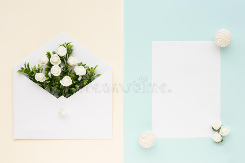 Workspace. Wedding invitation card, envelope, white roses and green leaves on beige blue background. Overhead view. Flat stock images