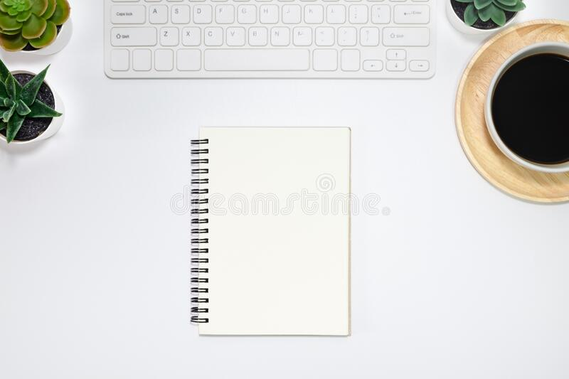 Workspace, White office desk table. View from above with keyboard, notebooks and white cup of black coffee on wooden plate. Top vi. Ew, flat lay with copy space stock photos