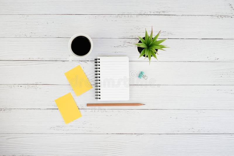 Workspace white wooden office desk table. With coffee cup and blank notebook, Sticky note and supplies, Top view with copy space, work space, flat lay royalty free stock image
