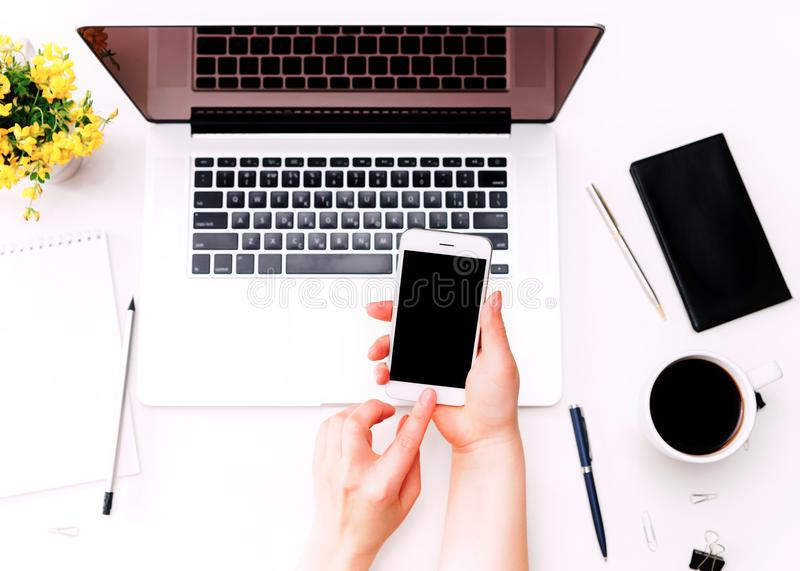 Workspace with woman hand holding phone laptop keyboard yellow flowers royalty free stock images