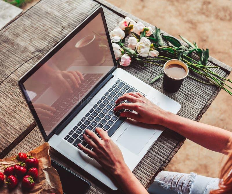 Workspace z dziewczyn rękami, laptop, bukiet peonie kwitnie, kawa, truskawki zdjęcie stock