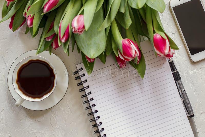 Workspace z kawą, telefon, notepad, pióro, czarna kawa i tulipany malinowy kolor, Odgórny widok obraz stock