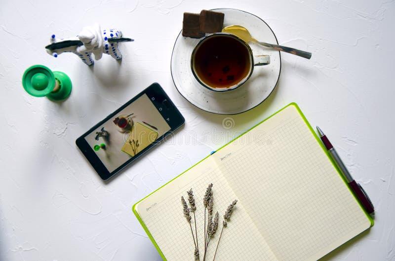 Workspace z notepad, filiżanka herbata na białym tle Mieszkanie nieatutowy, odgórnego widoku biurowy biurko pisze biurku Miejsca  obraz stock
