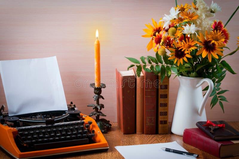Workspace z rocznik pomarańcze maszyna do pisania Bukiet lato kwiaty, świeczki i stare książki, fotografia stock