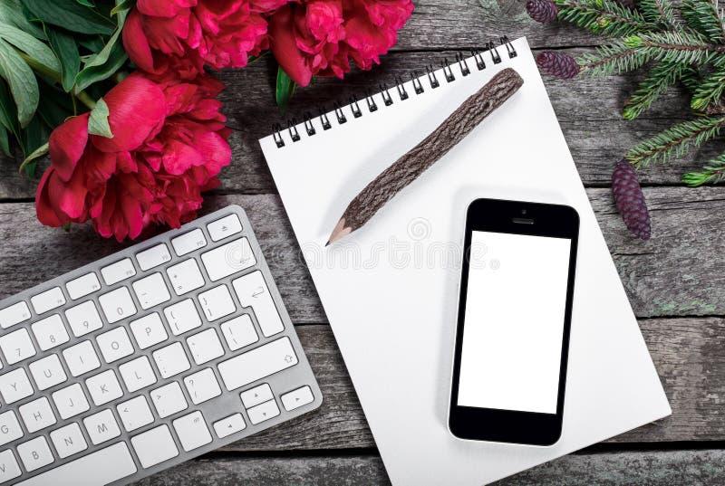 Workspace z smartphone, klawiaturą, notepad, drewnianym ołówkiem, jodły gałąź i peoniami, kwitnie bukiet na nieociosanym tle zdjęcie royalty free
