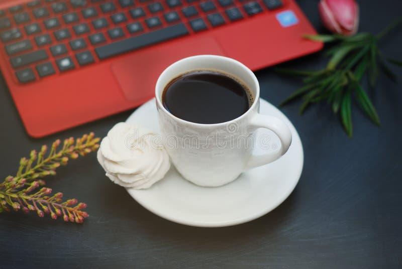 Worktable με το lap-top, φλιτζάνι του καφέ, πράσινα φύλλα Μορφή καρδιών, αγάπη Σκούρο μπλε, τονισμένος πίνακας Επίπεδος βάλτε στοκ εικόνα με δικαίωμα ελεύθερης χρήσης