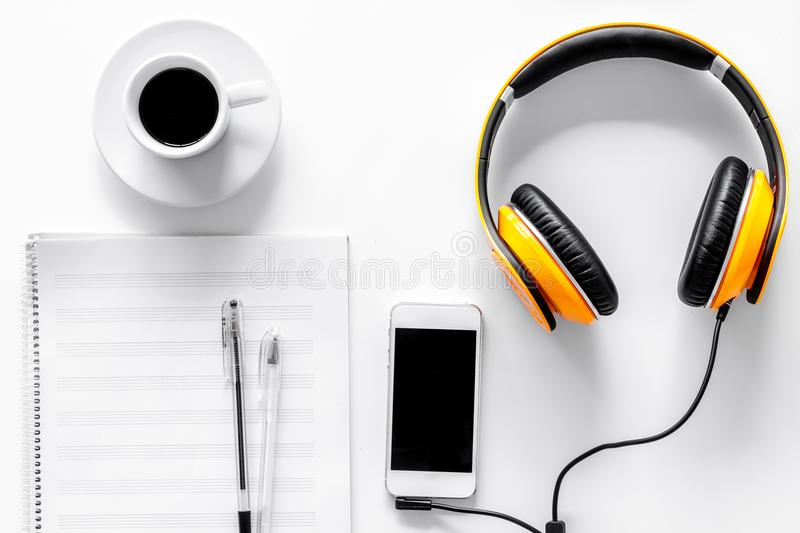 Worktable of composer today. Headphones, phone, music notes on white background top view royalty free stock photo