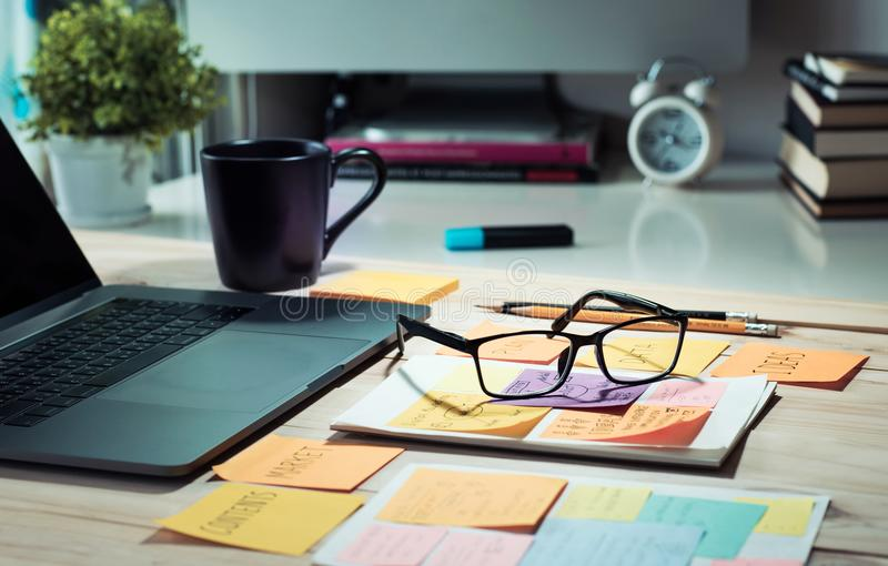 Worktable con il computer portatile del computer ed il blocco note, tazza di caffè nella mattina fotografia stock